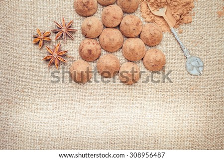 Chocolate truffles candies on a background of burlap bag texture with anise flowers, selective focus and vintage old style for chocolate day. There is a light spot for any text or design