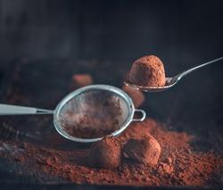 Chocolate truffles. Homemade fresh truffle dark chocolate candies with cocoa powder made by chocolatier. Gourmet food, delicious dessert. Closeup