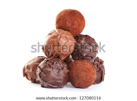 chocolate truffles put in the form of a pyramid on white background