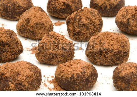 Chocolate truffles with cocoa powder on a white surface