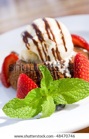 Chocolate volcano Lava cake A la Mode with strawberries, mint leaf and vanilla ice cream topped with chocolate syrup