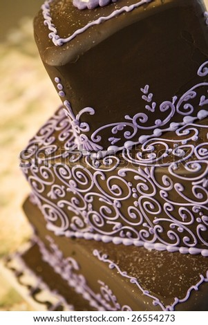 Chocolate wedding cake close up with details in purple.