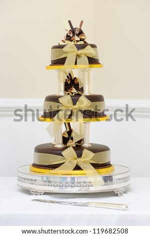 Chocolate wedding cake with gold decoration at reception