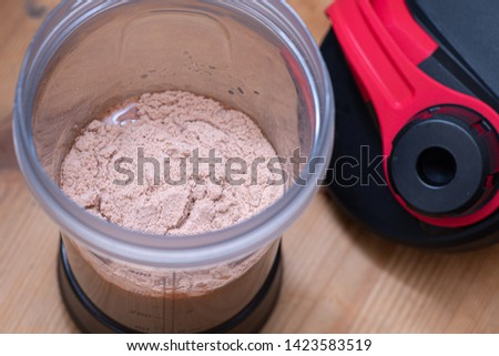 Chocolate whey protein powder a plastic shaker on wooden background.