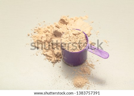 Chocolate whey protein powder with scoop on grey background