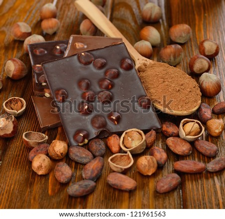 Chocolate with hazelnuts and cocoa beans on a brown table