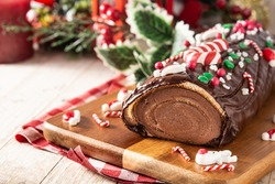 Chocolate yule log christmas cake on wooden table.Copy space