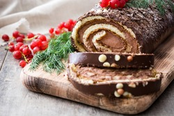 Chocolate yule log christmas cake with red currant on wooden background.closeup