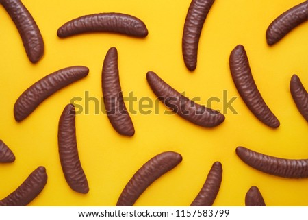 Chocolated coated bananas pattern on a yellow background viewed from above. Top view. Flat lay