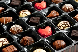 chocolates in a box, with red love heart shaped chocolate