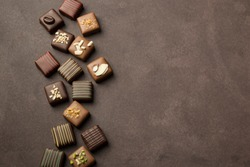 chocolates praline variety on brown background with copyspace