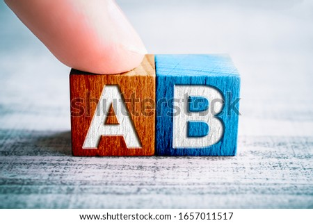 Choice A And B On Wooden Blocks On A Table, A Finger Touches Block A