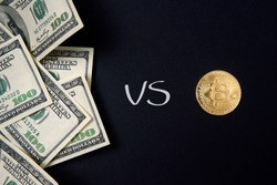 Choice among bundle of hundred dollar banknotes bills and bitcoin gold coin on black background isolated. US dollars vs cryptocurrency. Exchange bitcoin for a dollar.