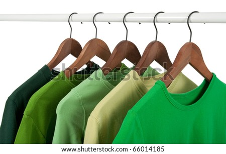 Choice of casual shirts on hangers, different tones of green. Isolated on white.