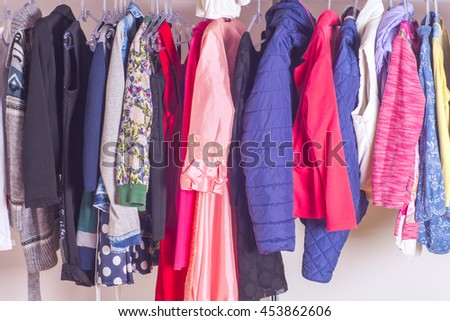 Choice of fashion clothes of different colors in walk-in clothing closet or store. Colorful choices of trendy outfits. Home living wardrobe. #453862606