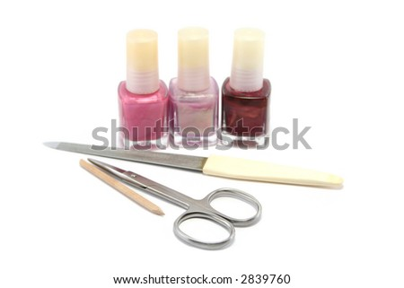 choice of pretty pinks and purple nail colours and a manicure set. Focus is on the scissors - stock photo
