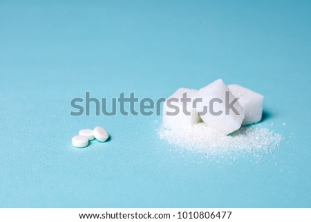 Choice of Sweetener in tablets or regular sugar. Alternative to sugar for people with diabetes. On a green background white sugar in cubes and sugar substitute in tablets