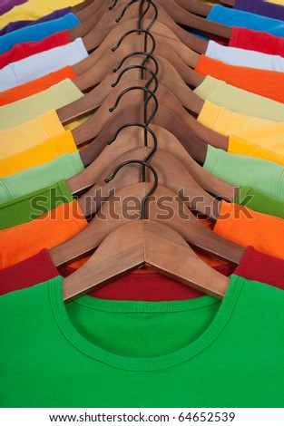 Choice of vibrant colorful t-shirts on wooden hangers.