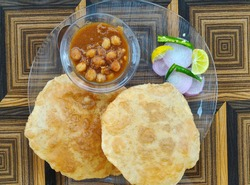 Chola bhatura. Famous Indian meal chik peas curry with flour fried poori or puri and salad.