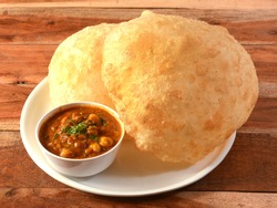 Chole Bhature, spicy Chick Peas curry also known as Chole or Channa Masala is traditional North Indian main course recipe and usually served with fried puri or Bhature, selective focus