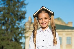 Choose book for school literature. Happy kid with book on head. Literature lesson. English literature. Childrens literature. Foreign language. School library. Homework. Examination. Back to school.