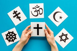 Choose religion concept. Hand with catholic cross near world religions symbols on blue background top view