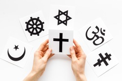 Choose religion concept. Hand with catholic cross near world religions symbols on white background top view