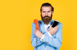 Choose your World. Then and Now. mature bearded man talk on retro phone. male hold smartphone. compare technology. mobile phone vs retro phone. business call. concept of technology progress.