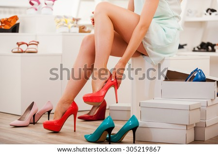 Choosing right shoes for today. Close-up of young woman trying on different shoes while sitting in the shoe store