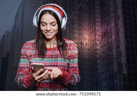 Choosing songs. Pleasant positive smiling woman looking at the screen of her smart phone while listening to music in her new big headphones #751098571