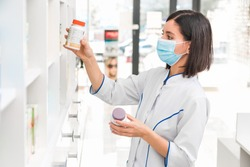 choosing the right medicine. professional looking female pharmacist with medical mask on in drug store studying the prospectus of a new drug
