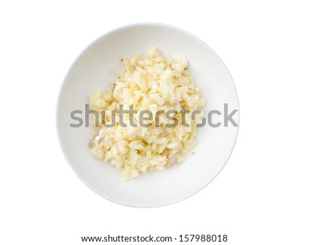 chopped and slices of garlic in white bow on wooden table