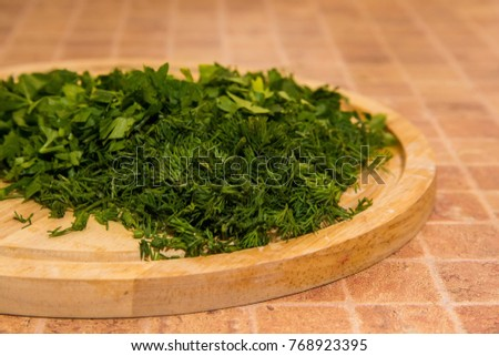 Chopped dill and parsley on wooden board #768923395
