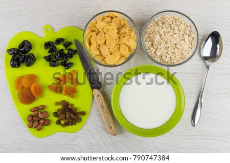 Chopped dried fruits and peanuts on cutting board, bowls with corn flakes, oat flakes and yogurt, knife and spoon on wooden table. Top view #790747384