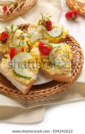 Chopped eggs with cucumber and strawberries on toast