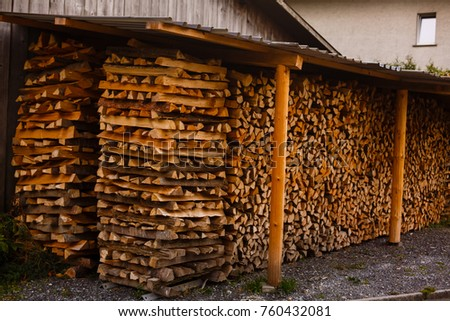Chopped firewood stacked in a woodpile under a canopy #760432081