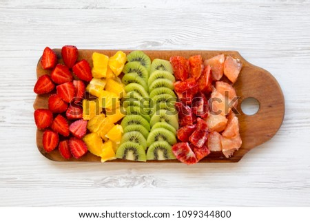 Chopped fruits arranged on cutting board on white wooden background, top view. Ingredients for fruit salad. From above, flat, overhead.
