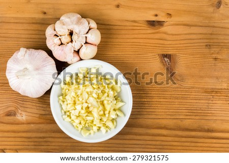 Chopped garlic in a plate with garlic bulbs on wooden table