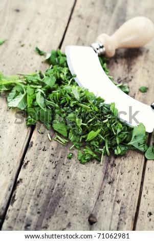 chopped herbs on cutting board with a mezzaluna