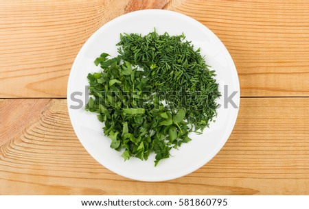 Chopped parsley and dill in saucer on wooden table. Top view #581860795