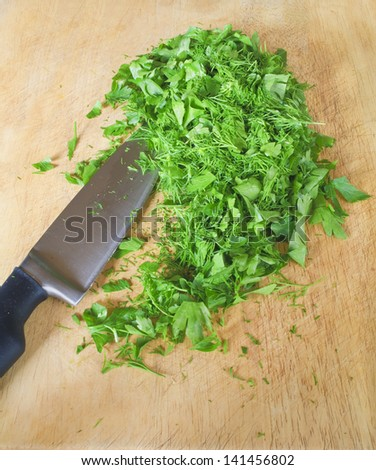 chopped parsley and dill, with knife on kitchen board #141456802