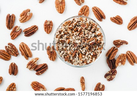 chopped pecans for baking on a white textured background Foto stock ©