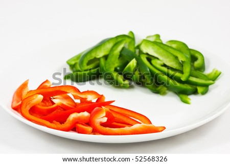 Chopped red and green peppers separated on a white plate, with a white background and copyspace for your text.