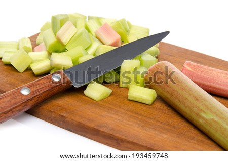 Chopped rhubarb on a wood cutting board, isolated on white