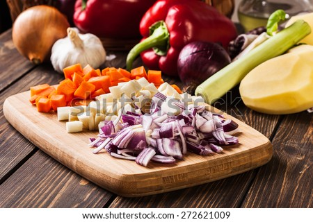Chopped vegetables: carrots, parsley and onion on cutting board