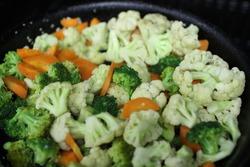 Chopped vegetables, cauliflower, and broccoflower on black pan.