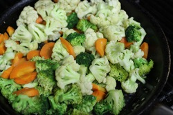 Chopped vegetables, cauliflower, and broccoflower on black pan.