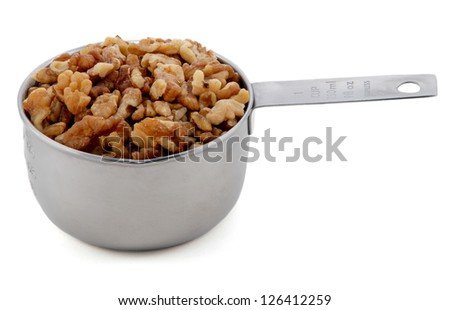 Chopped walnuts presented in an American metal cup measure, isolated on a white background