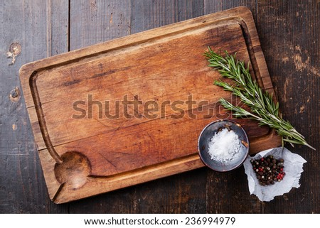 Chopping board, seasonings and rosemary on dark wooden background Foto stock ©