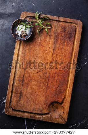Chopping cutting board, seasonings and rosemary on dark marble background